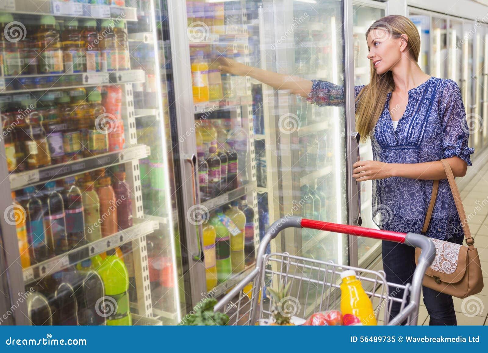 Une femme prenant une bouteille dans le bas-côté congelé