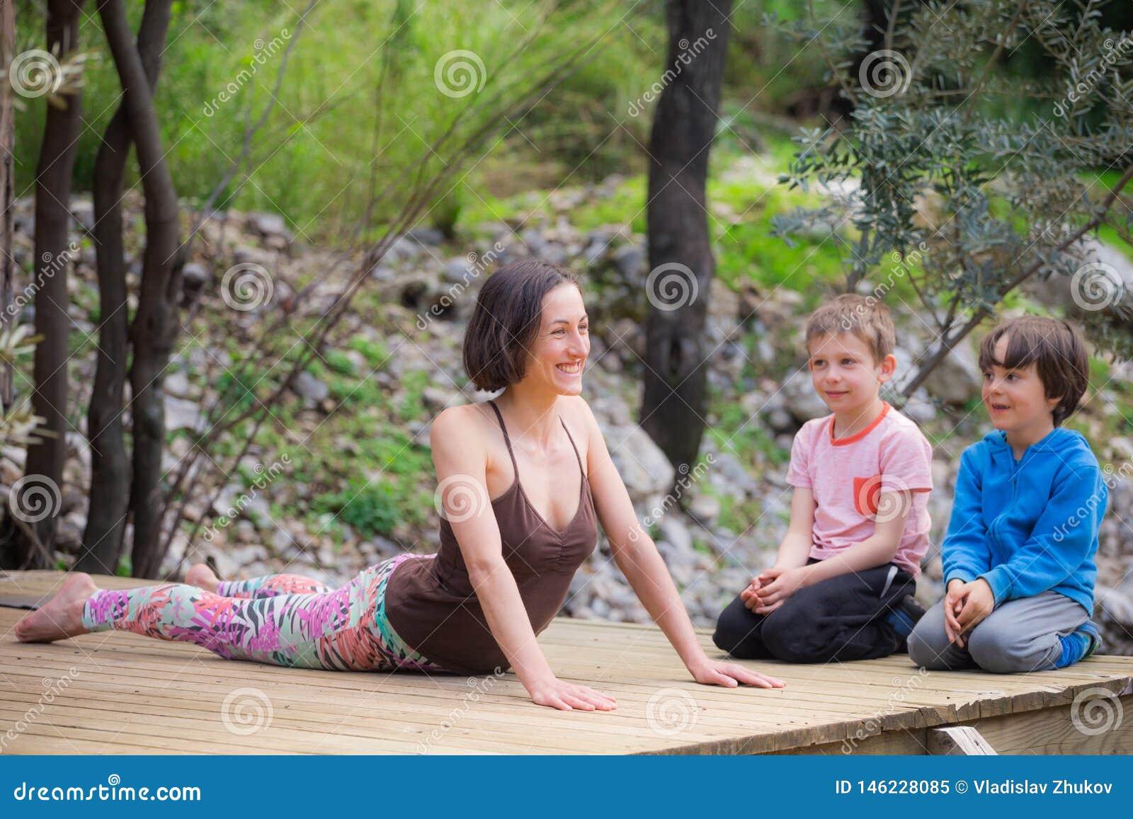 Une femme s exerce avec des enfants dans la cour