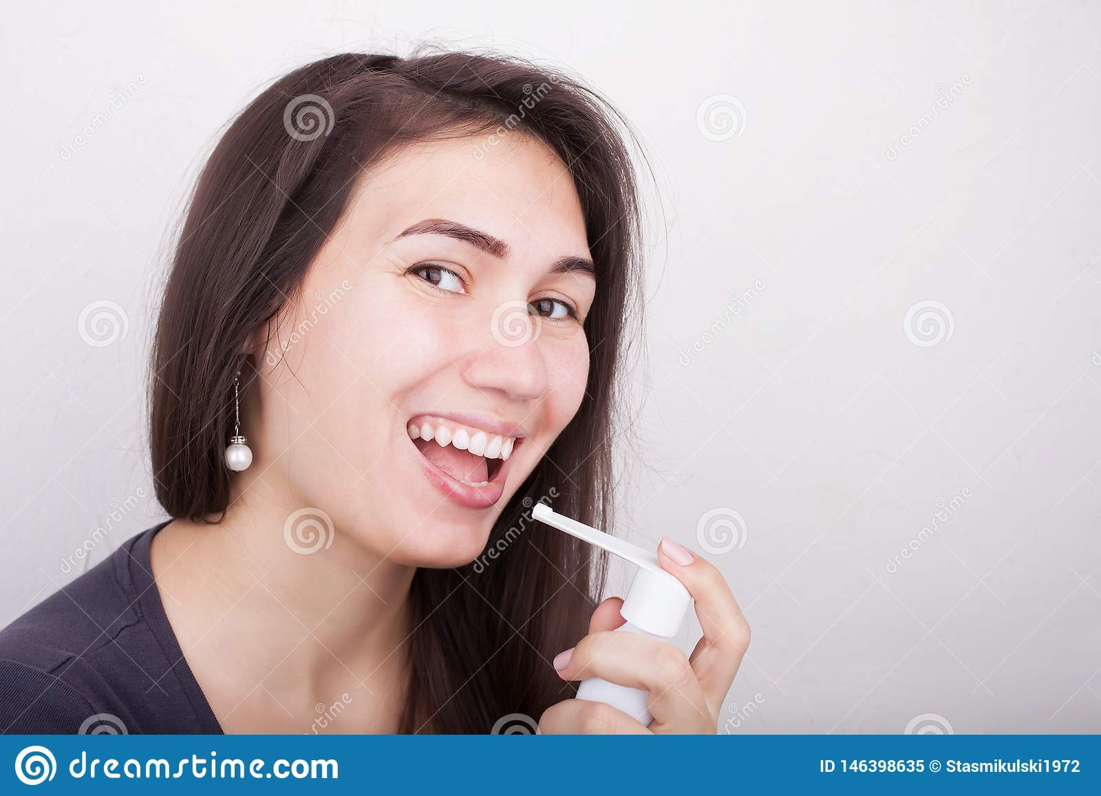 Une femme tient un pulvérisateur pour la médecine de gorge