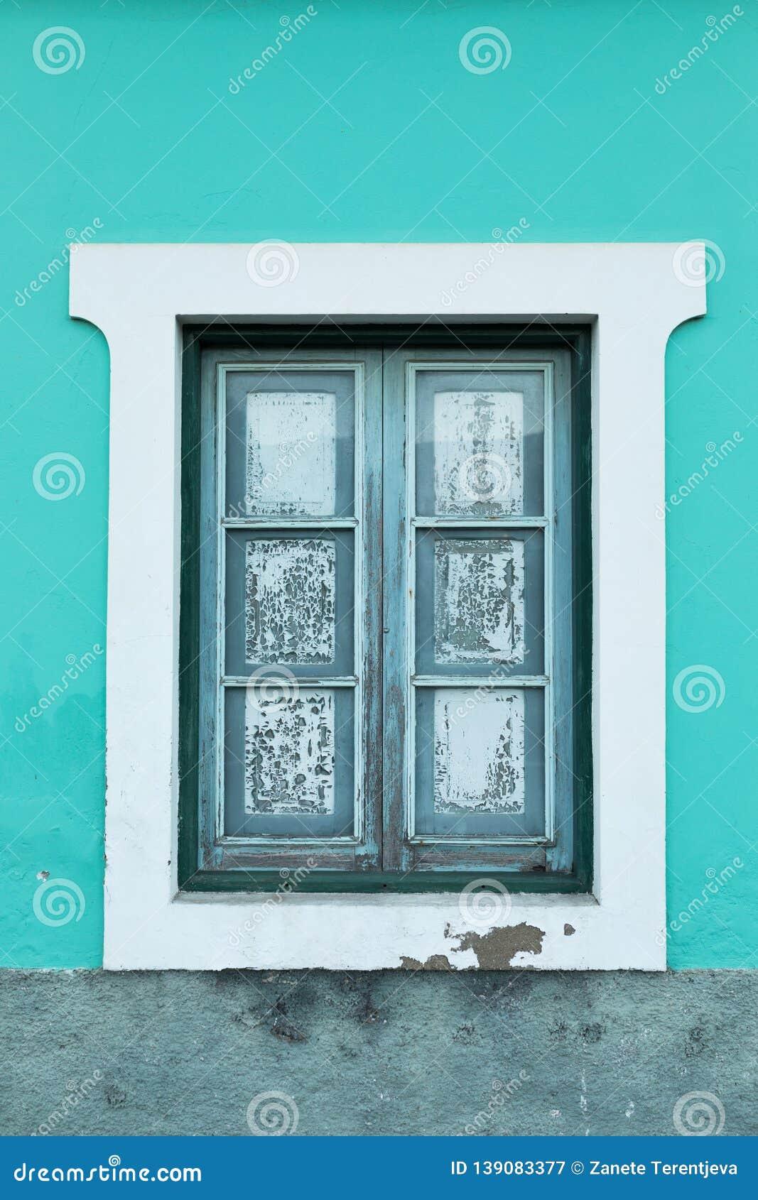 Une fenêtre d une aigue-marine lumineuse, maison de couleur de turquoise avec un vieux cadre en bois et une peinture blanche auto
