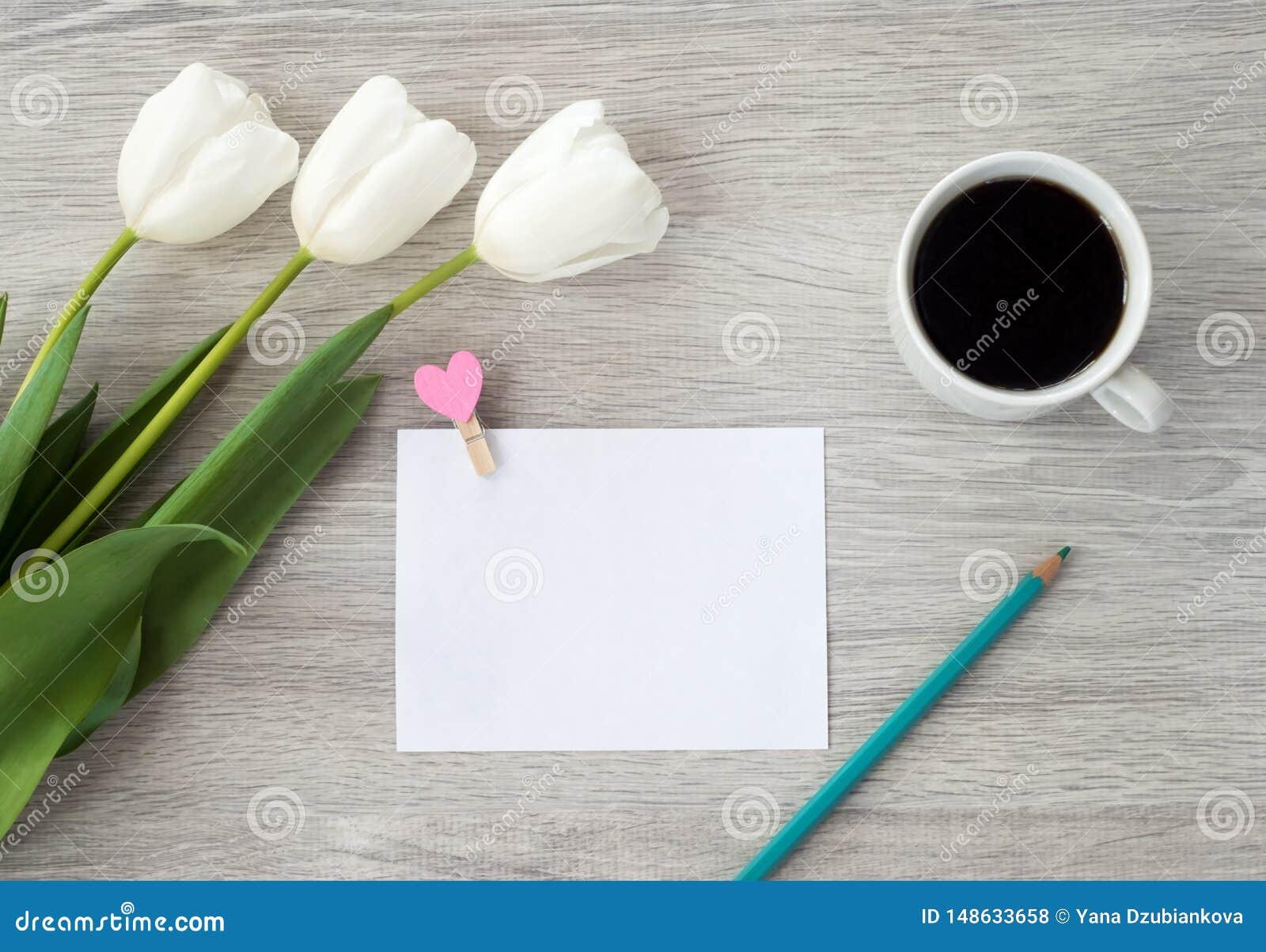 Une feuille de papier avec un stylo rouge, des fleurs et une tasse de mensonges de café sur une table en bois blanche Laissez une