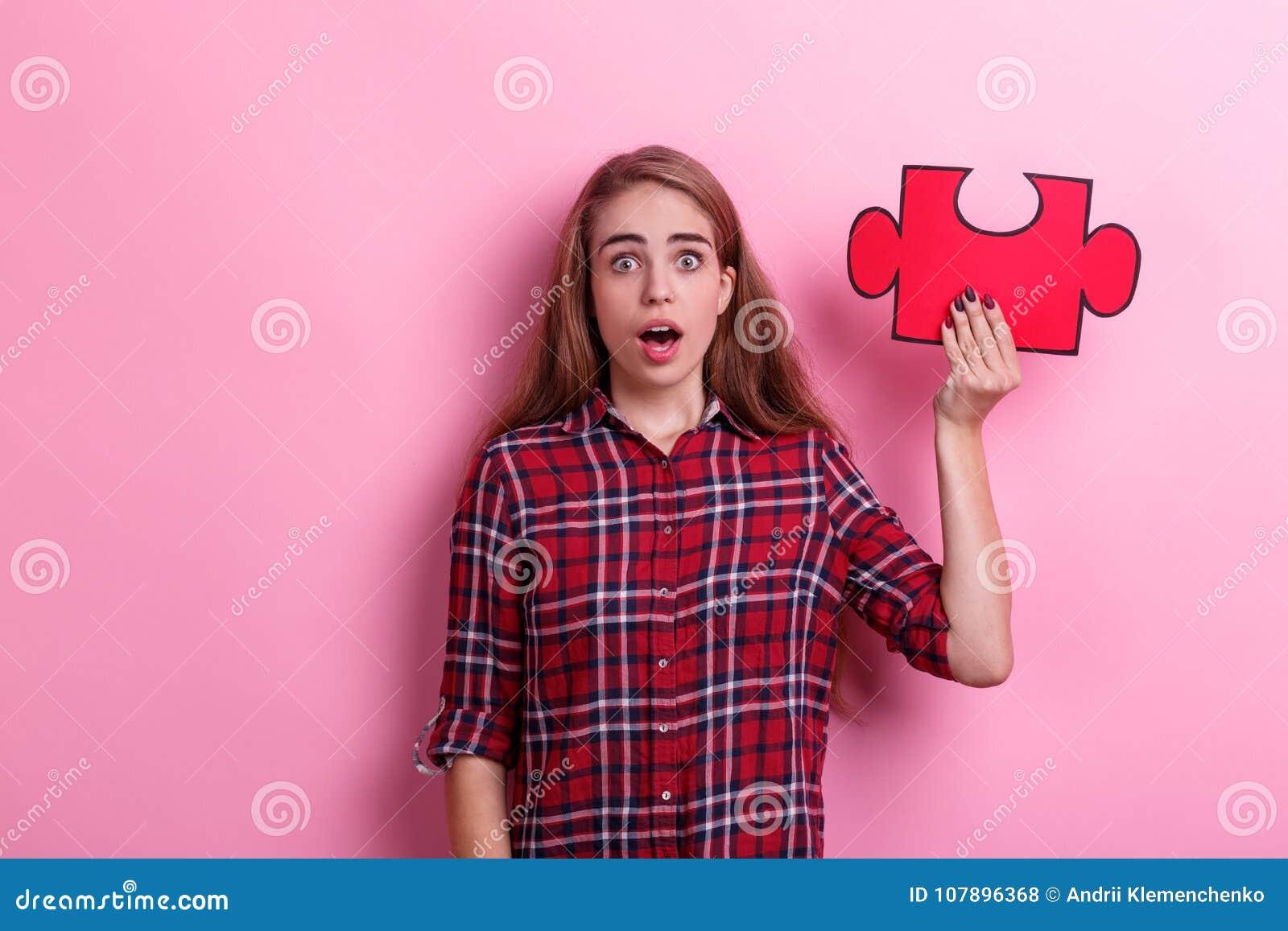 Une fille étonnée, prises un grand puzzle sur la main augmentée avec la bouche ouverte Sur un fond rose