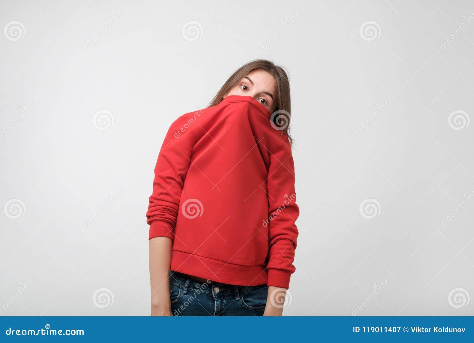 Une fille avec une phobie sociale cache son visage dans un chandail