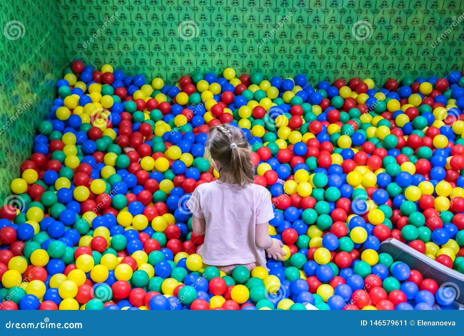 Une fille dans la piscine avec beaucoup de boules colorées dans les enfants jouant la pièce
