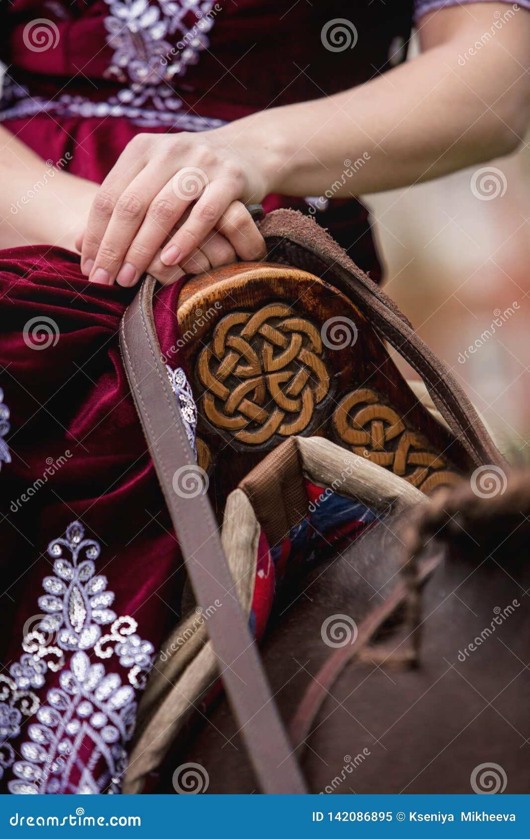 Une fille dans la robe classique tapote son cheval sur le fond du château