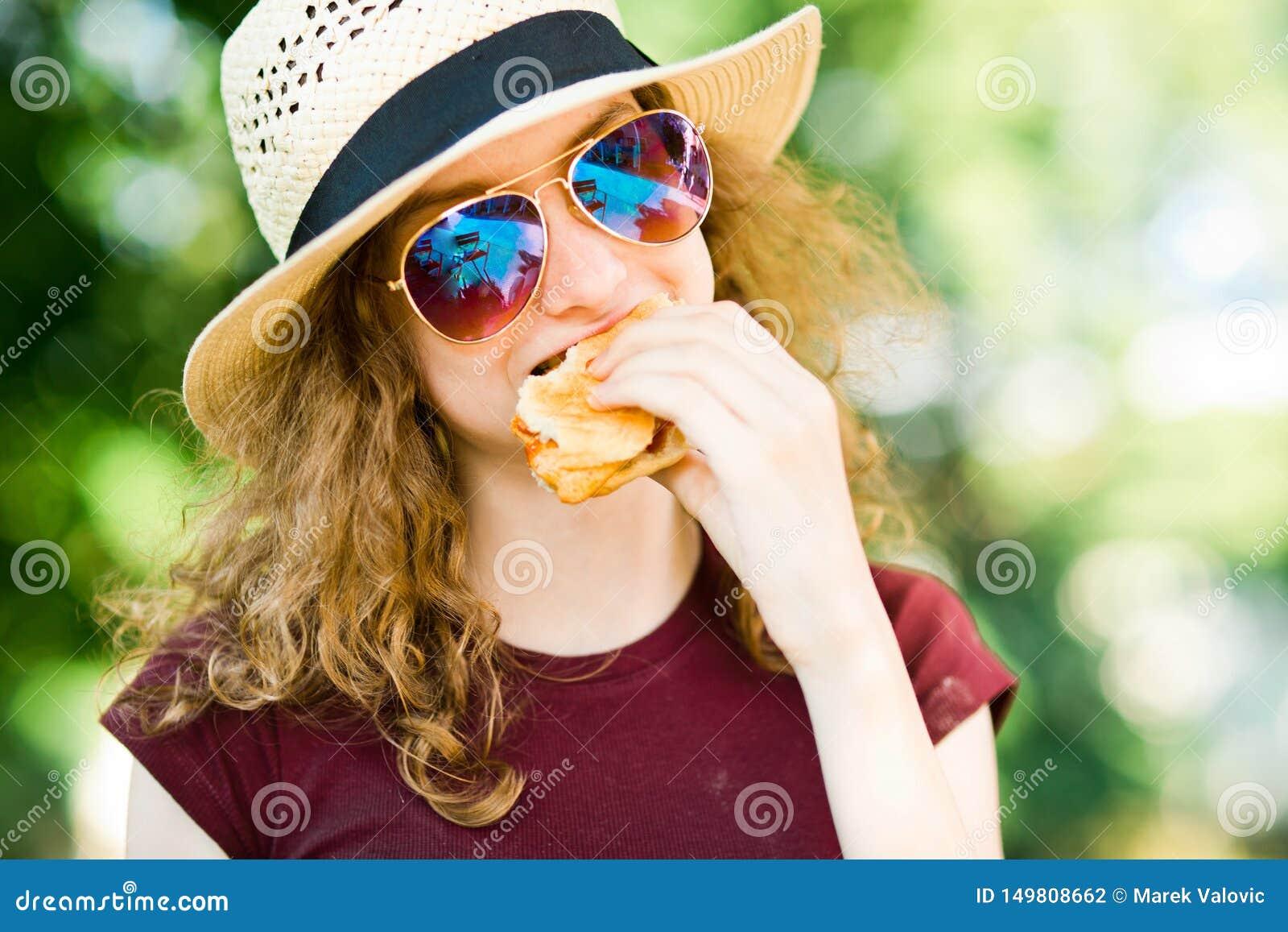 Une fille dans le chapeau avec l hamburger en verre de soleil mordu