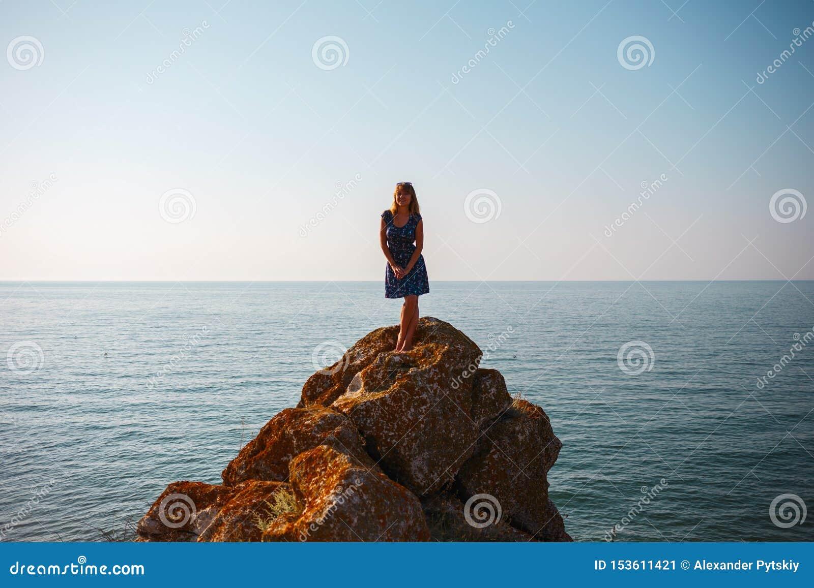 Une fille dans une robe se tient sur une pierre et des regards à la mer bleue