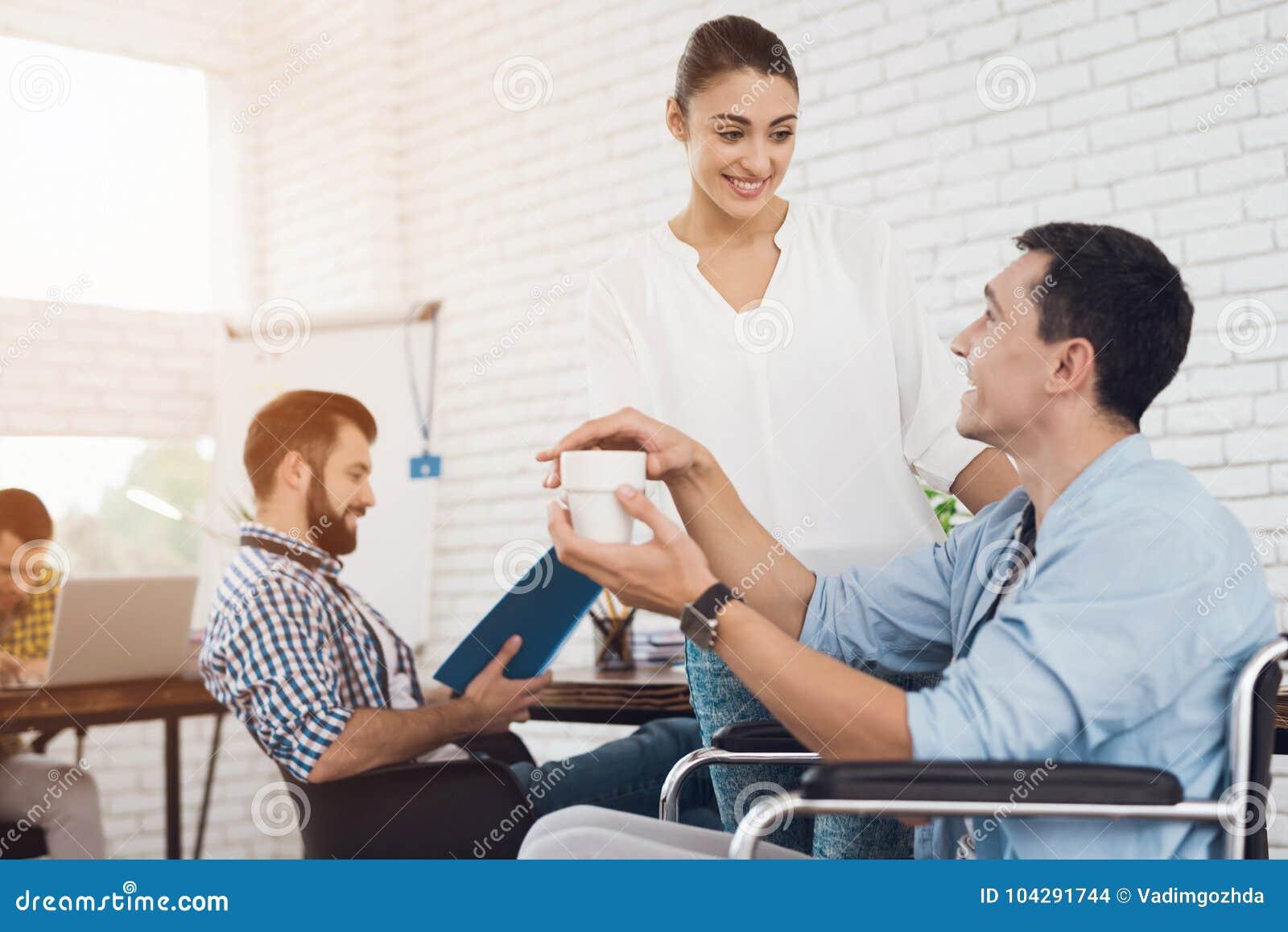 Une fille donne à un handicapé dans un fauteuil roulant par tasse