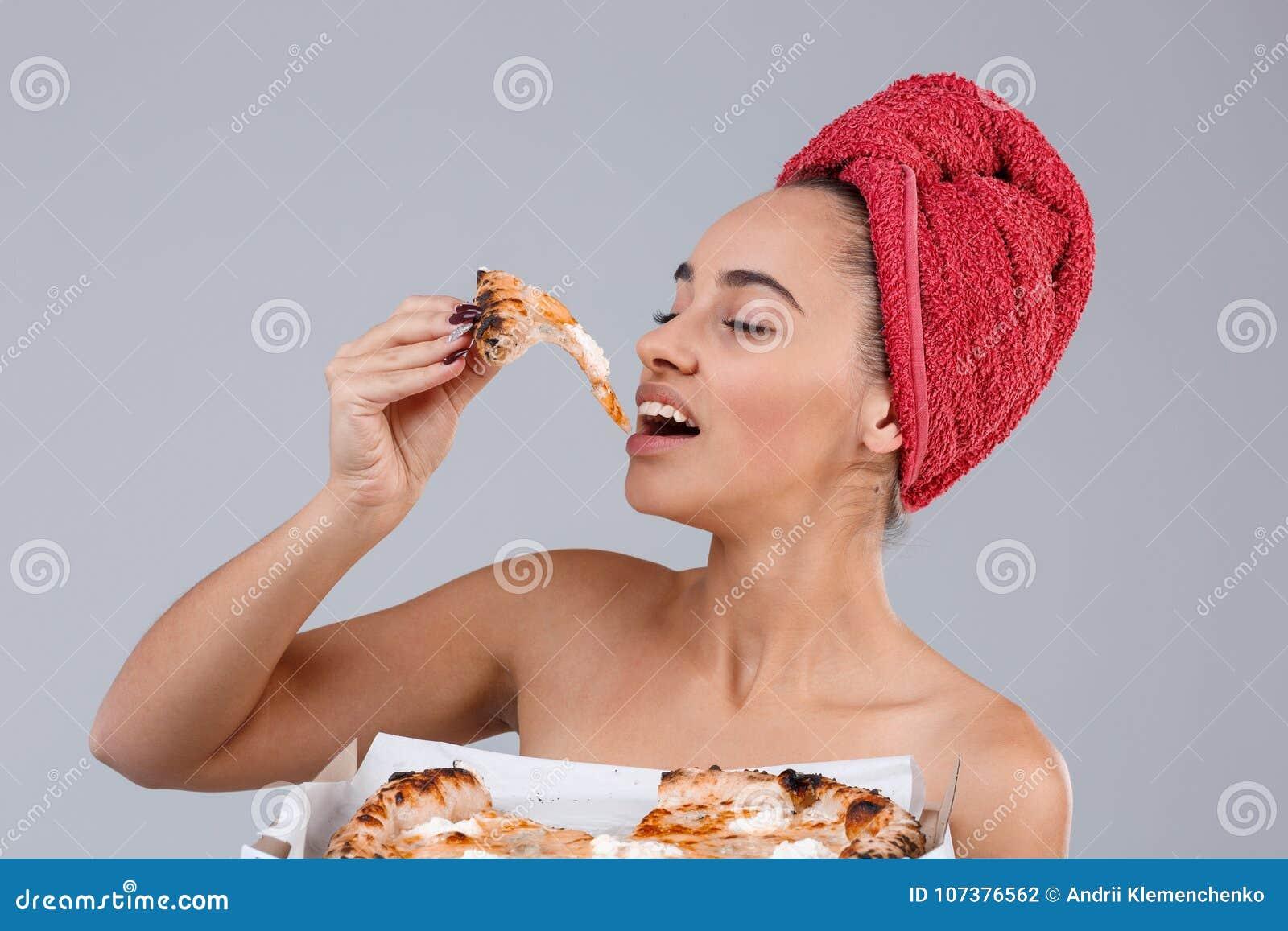 Une fille est enveloppée dans une serviette sur le chef, mangeant un morceau de pizza sur un fond gris