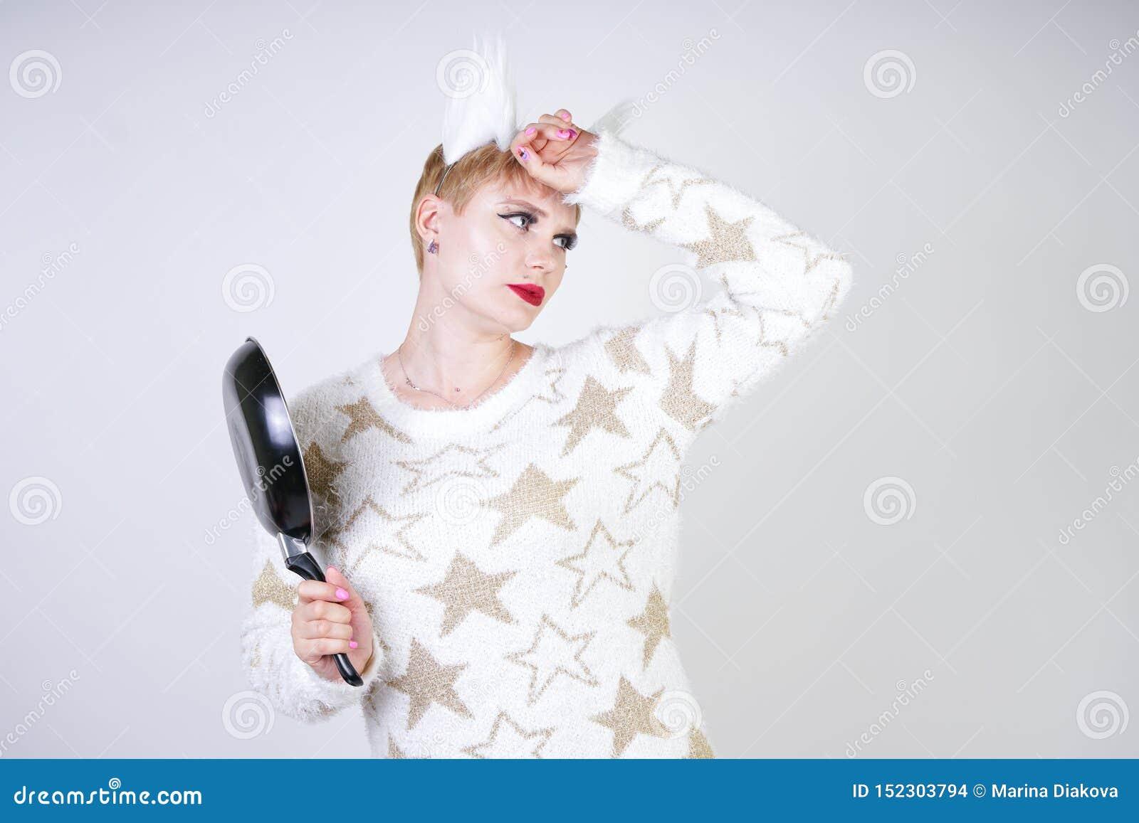 Une fille fâchée avec les cheveux blonds courts dans un chandail pelucheux avec des oreilles de fourrure femme plus mauvaise de t