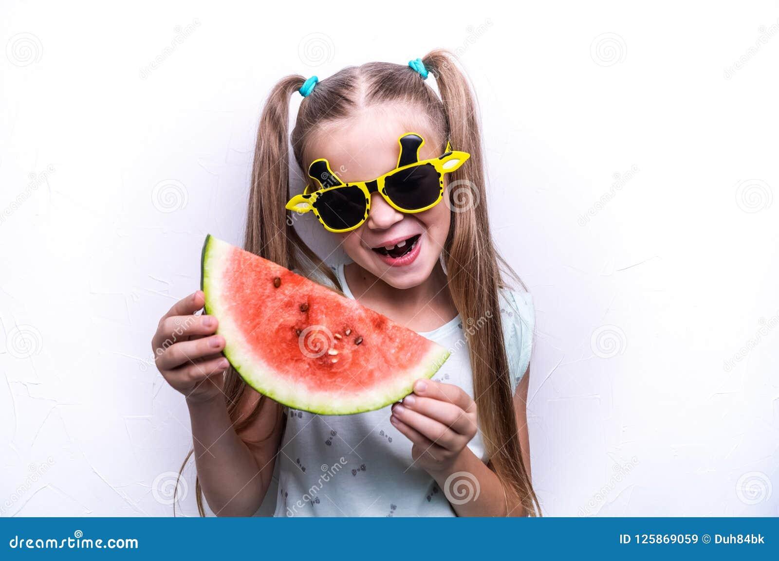 Une fille heureuse, un enfant dans des lunettes de soleil jaunes, mange une pastèque rouge mûre Portrait