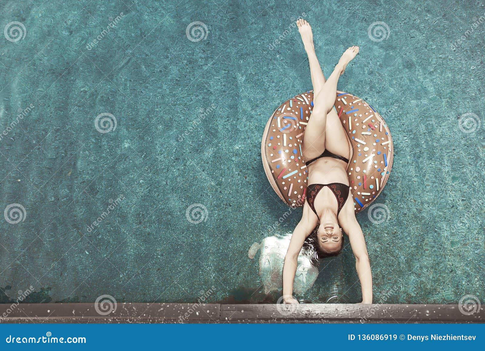 Une fille sur un cercle flotte sur l eau