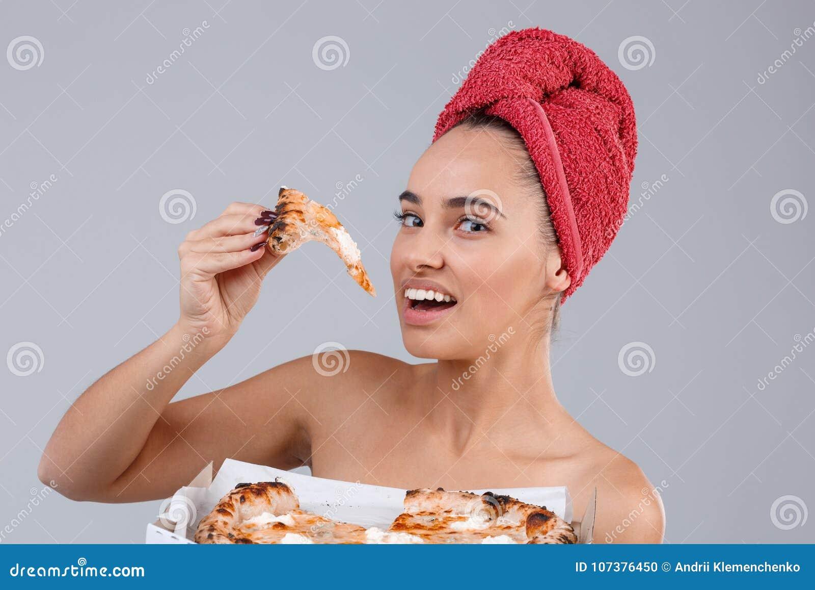 Une fille tenant une bouchée du morceau de pizza appétissant sur un fond gris