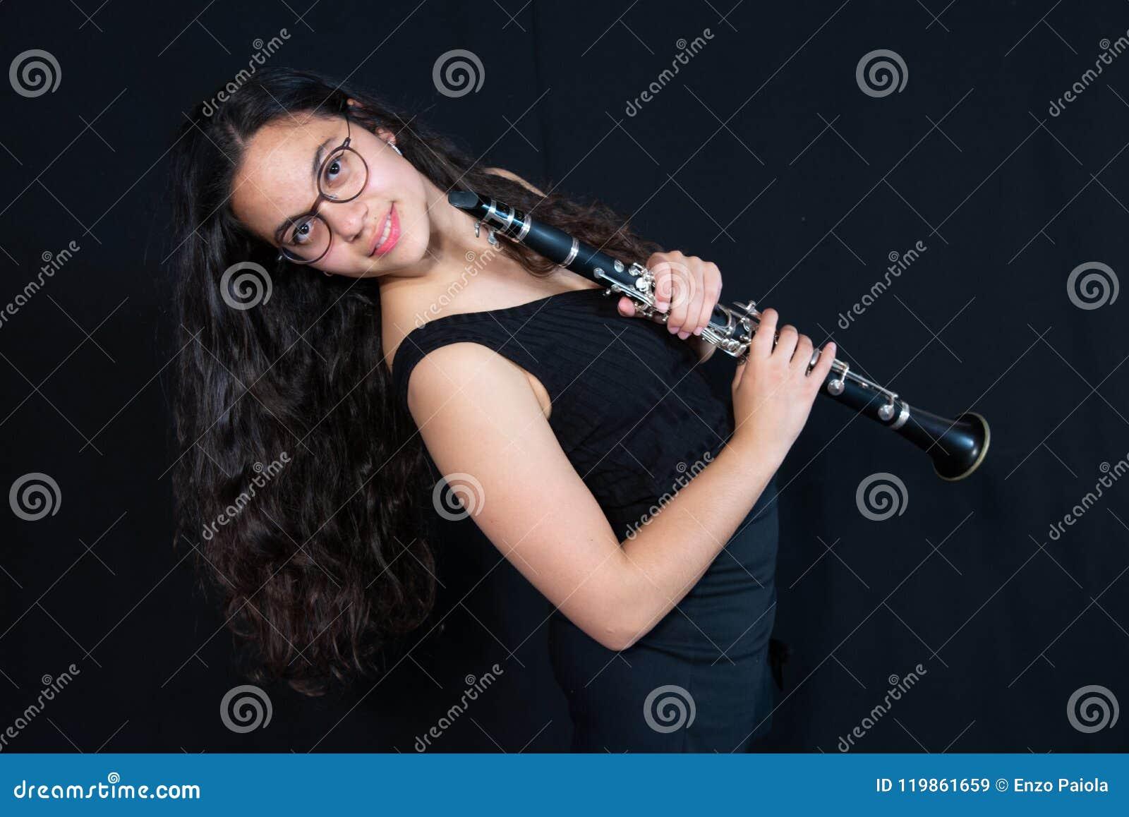 Une fille tenant son instrument de musique de clarinette Figure sur un fond noir