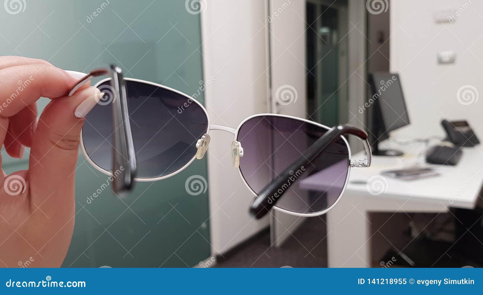 Une fille tient les lunettes de soleil à la mode dans sa main et les voit une salle vide de bureau