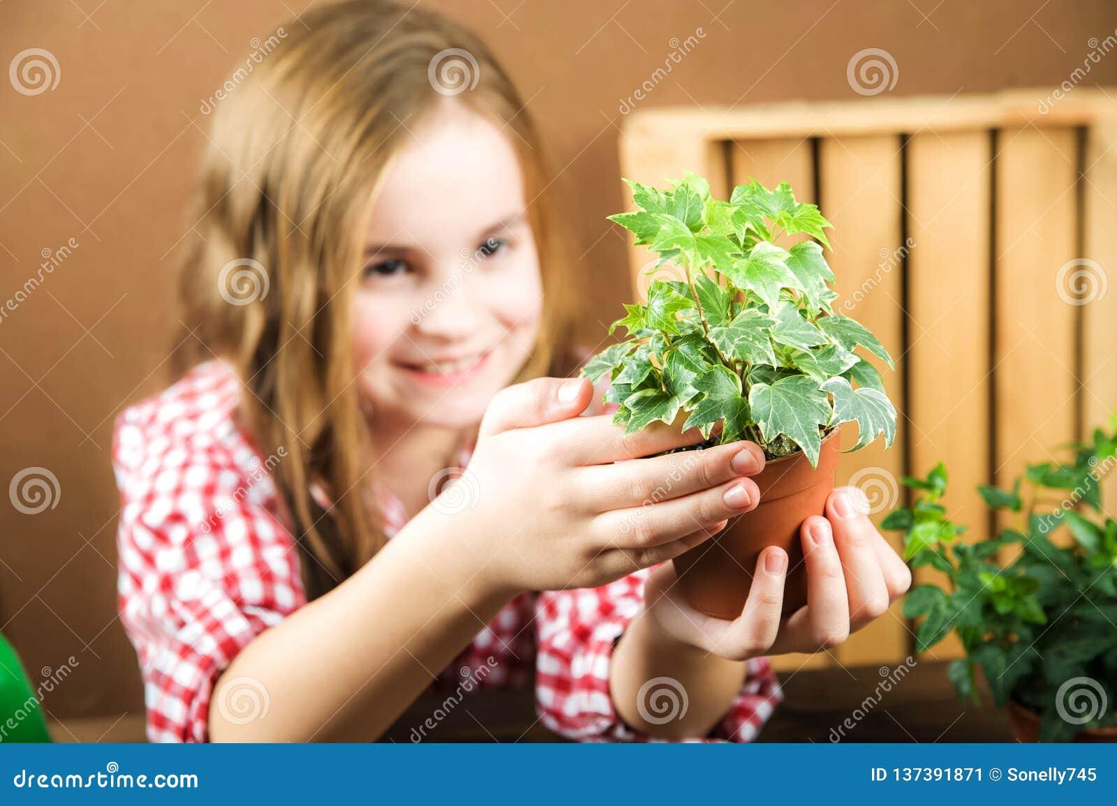 Une fille tient un pot avec une fleur une fille dans une chemise de plaid dans des ses mains une terre avec le lierre de bruyère