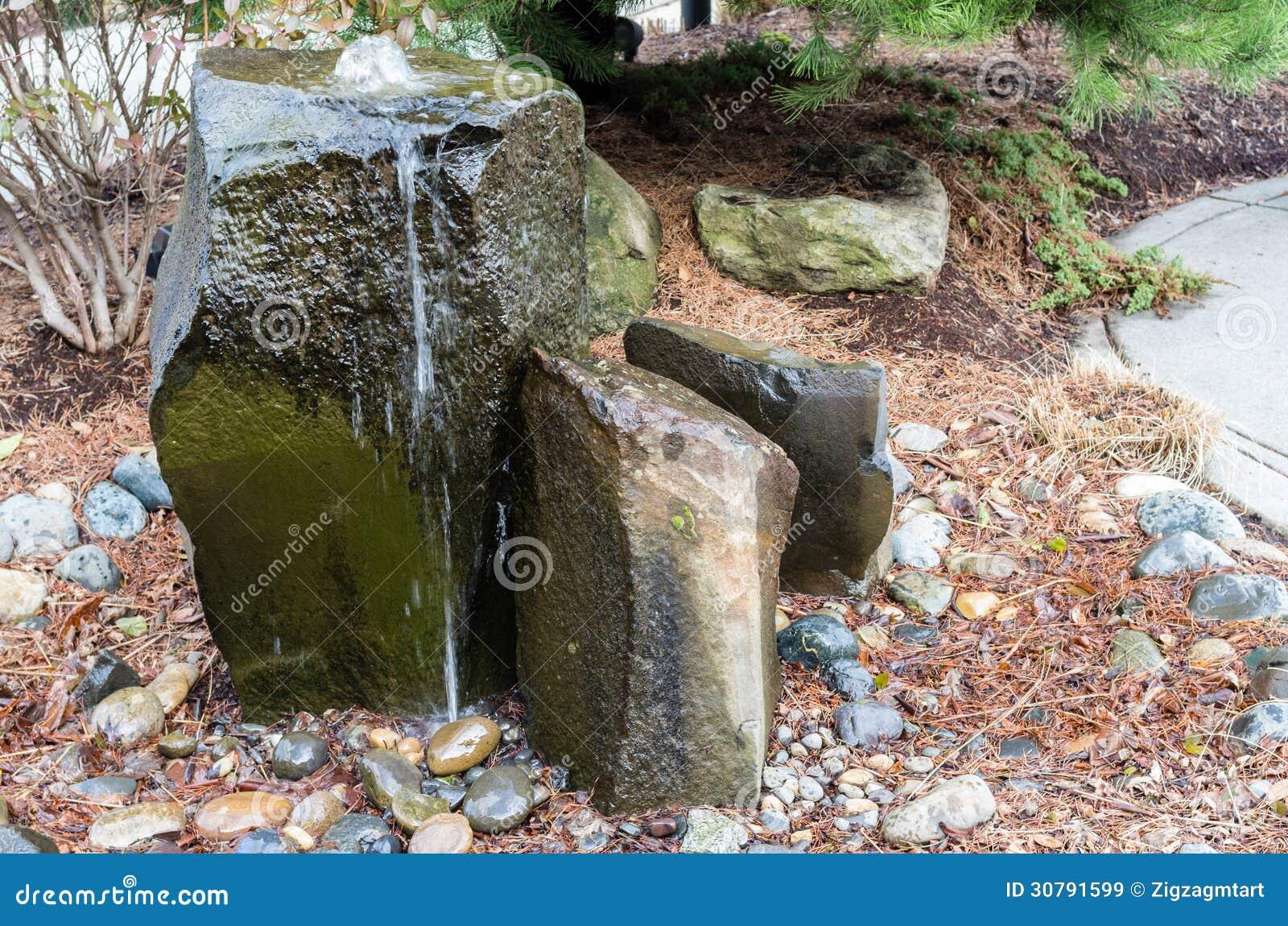 Une fontaine d 39 eau de bouillonnement rocheuse dans un jardin de cour images libres de droits for Fontaine de jardin oslo