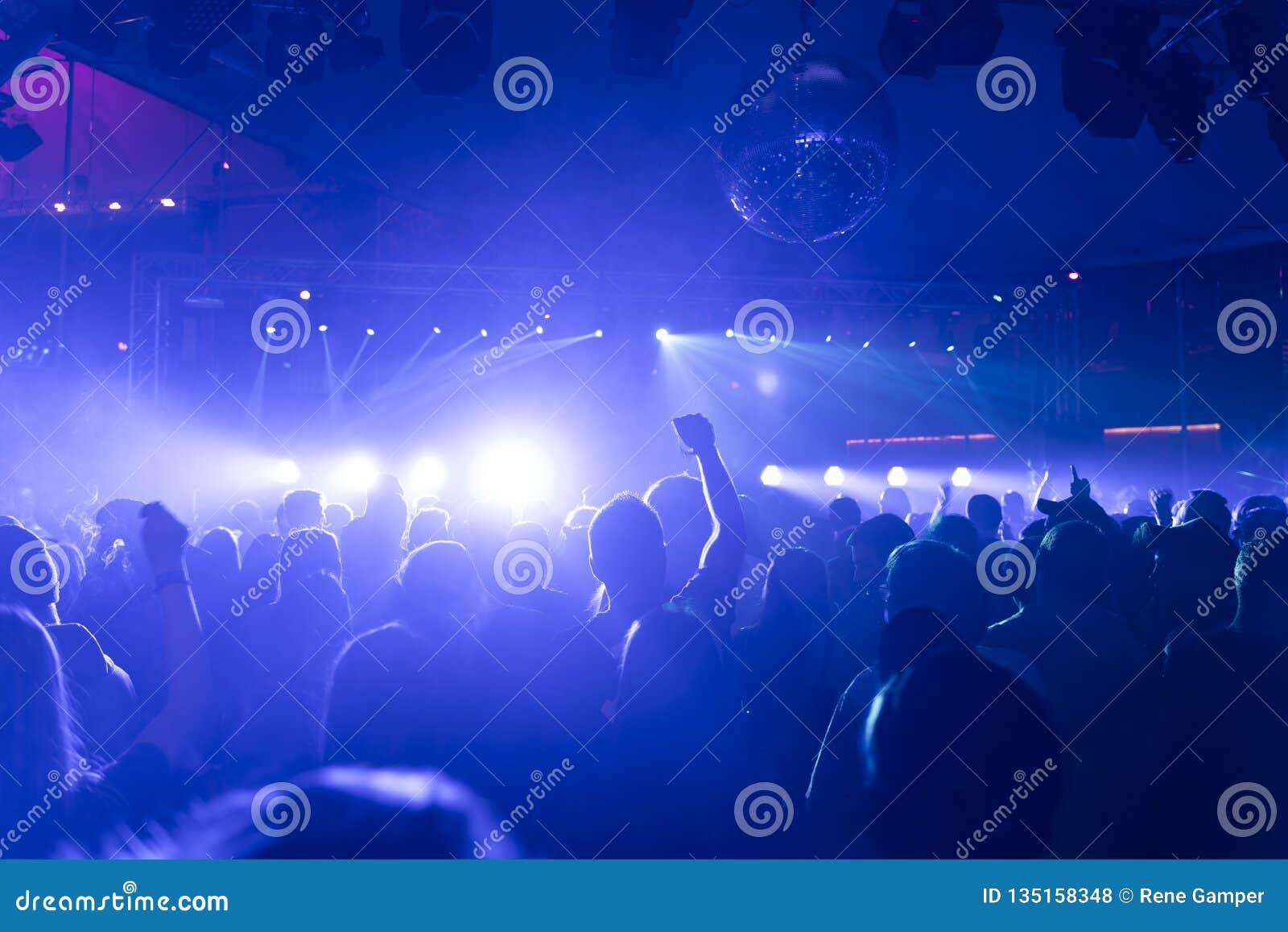 Une foule des personnes faisant la fête dans un club de disco, une lumière et des lasers et un environnement brumeux