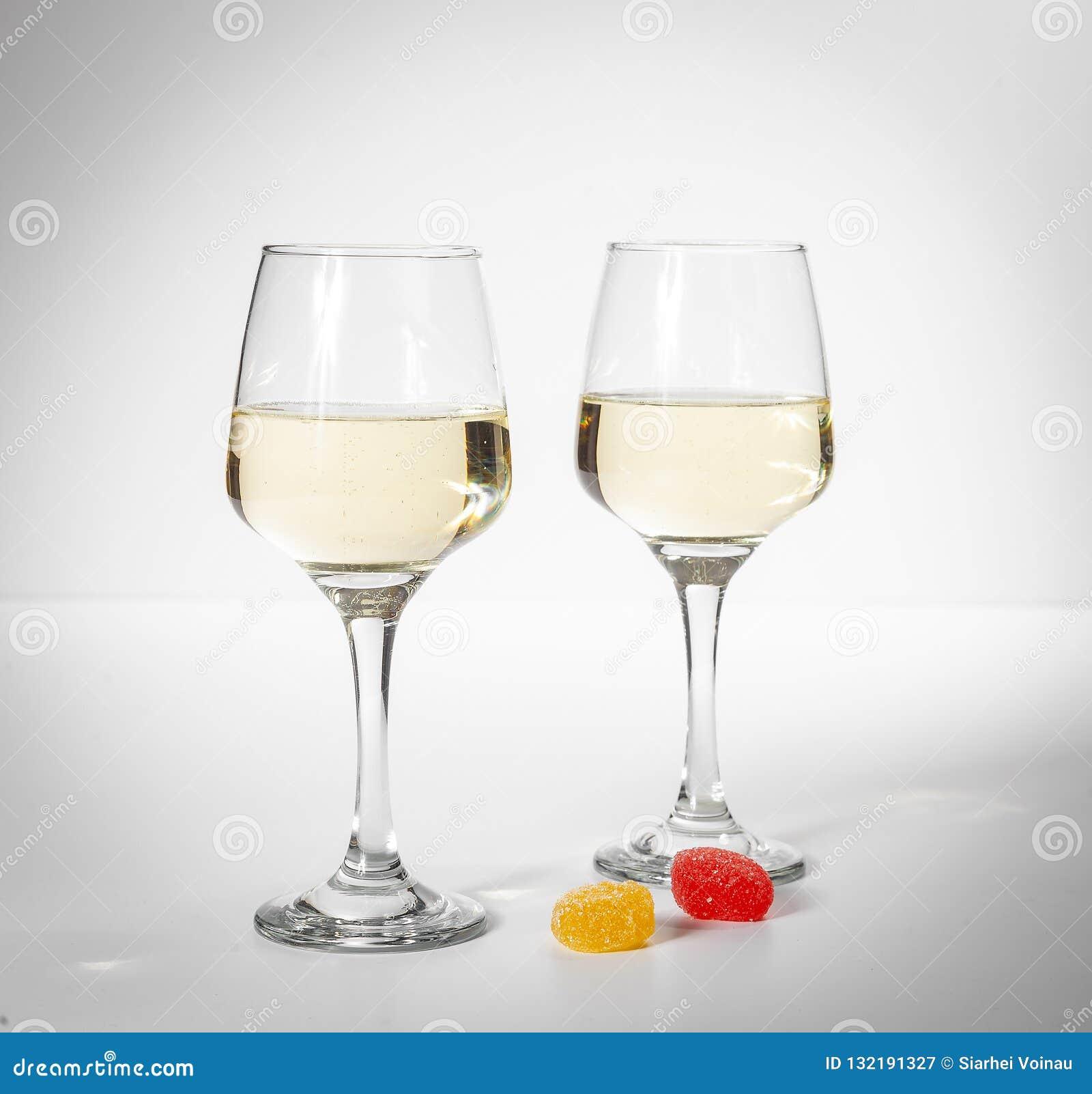 Une glace de vin blanc Sucreries multicolores sur un fond blanc