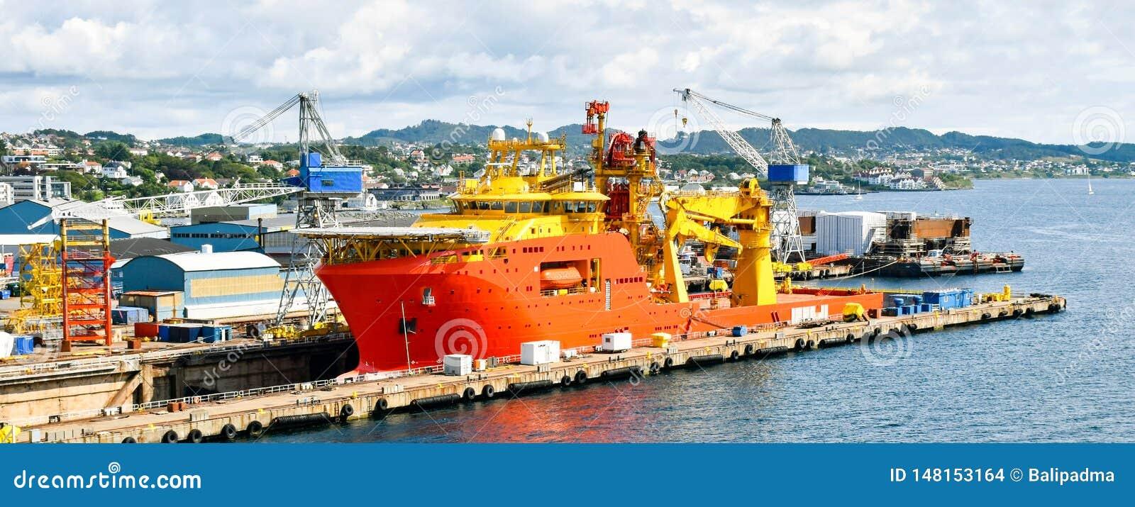 Une grande orange et un navire en mer color? jaune OCV de construction est dans un dock sec d un chantier naval et est r?par?e