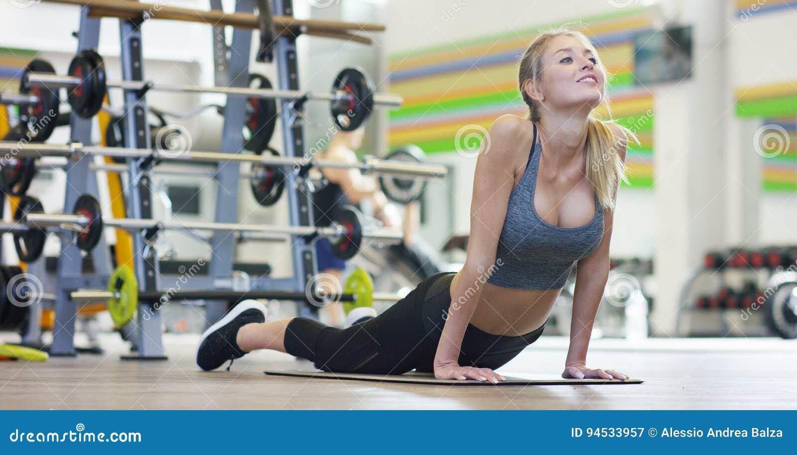 Une jeune belle fille dans un gymnase, se penchant sur ses mains, secoue la presse, faisant de longues étapes, pliant ses genoux