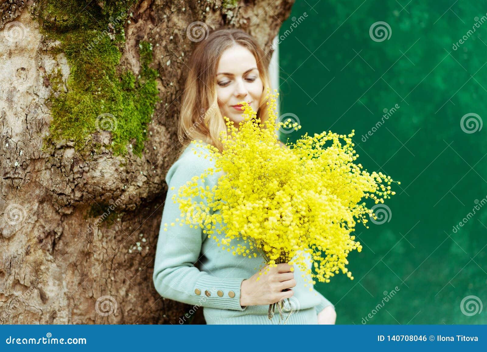Une jeune femme élégante est sourire, tenant un présent dans sa main un bouquet des fleurs fraîches de mimosa