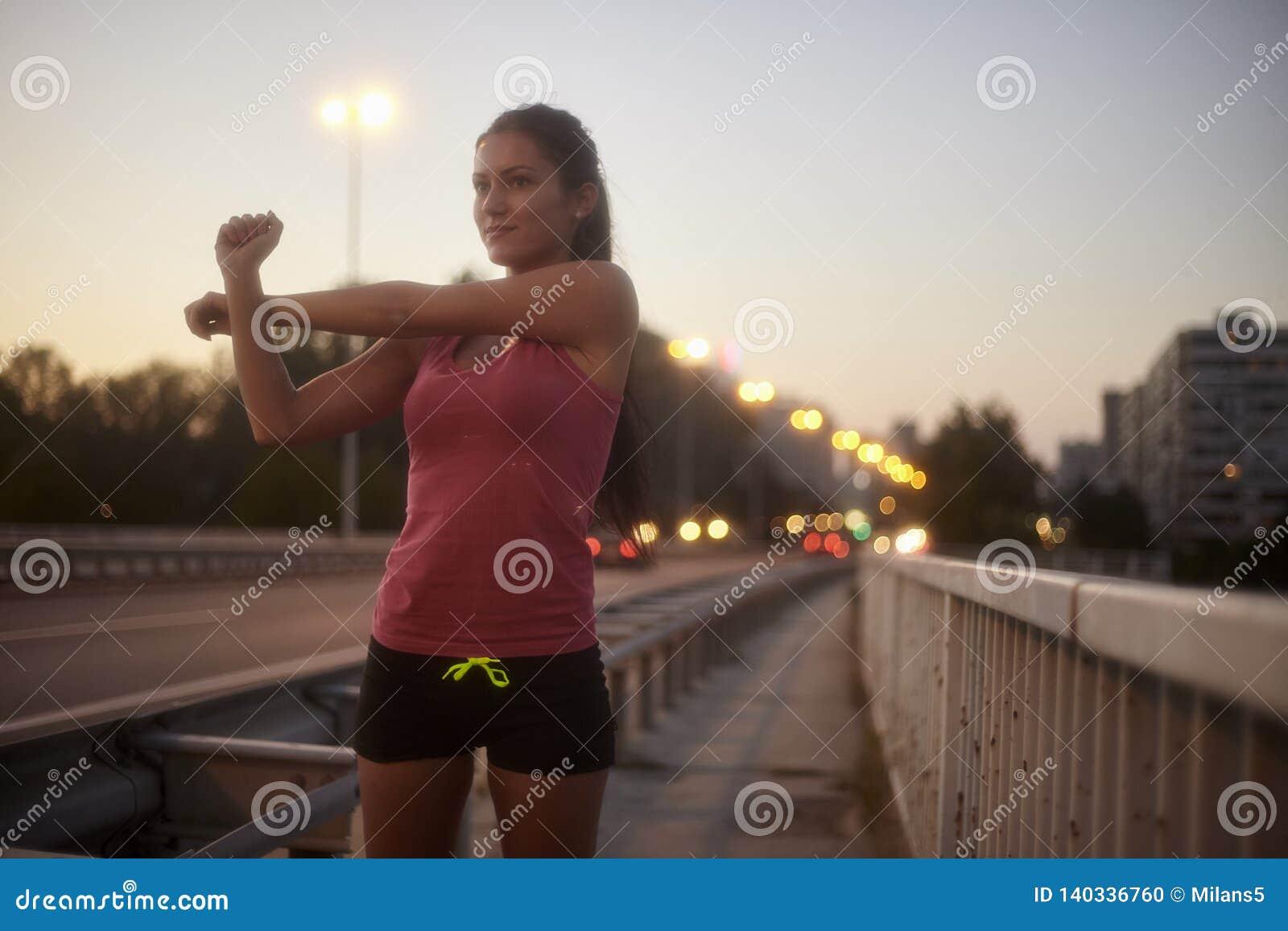 Une jeune femme, 20-29 ans, tir de corps supérieur, souriant d un air affecté tout en étirant des bras dehors sur un pont
