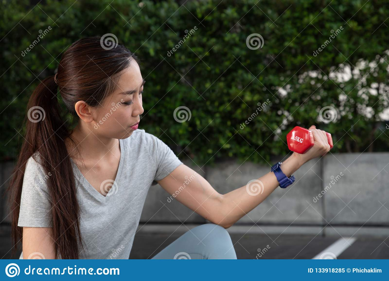 Une jeune femme asiatique se soulevant vers le haut d un drumbell rouge