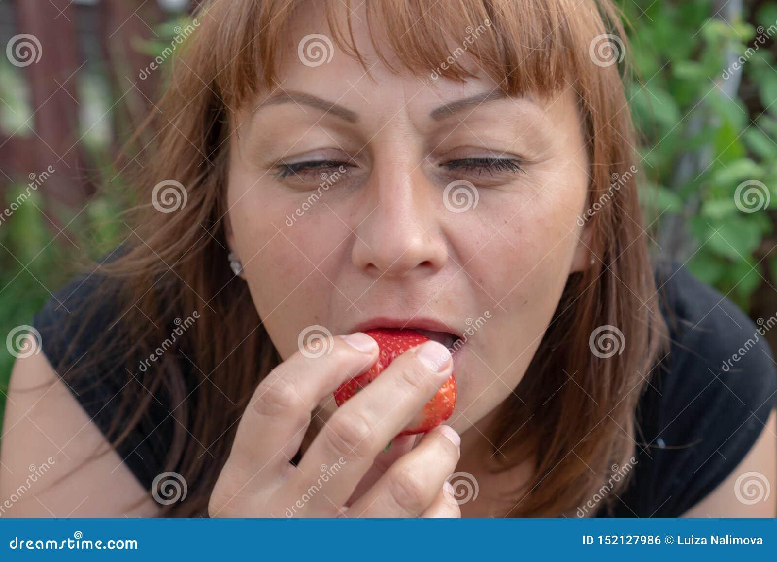 Une jeune femme avec les cheveux rouges mord les fraises mûres et ferme ses yeux avec plaisir