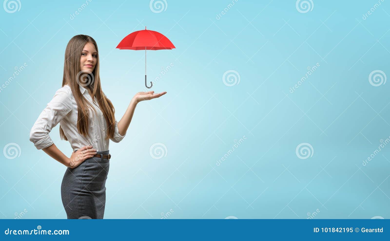 Une jeune femme d affaires soutient un petit parapluie rouge ouvert sur sa paume ouverte