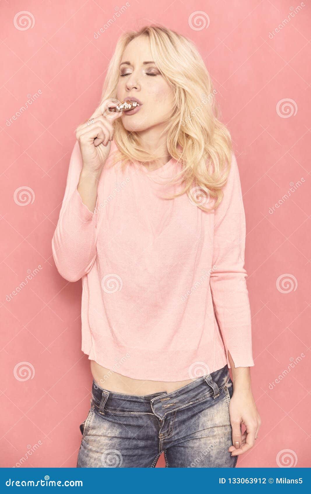 Une jeune femme, mangeant du chocolat et appr?ciant vraiment avec ses yeux ferm?s,