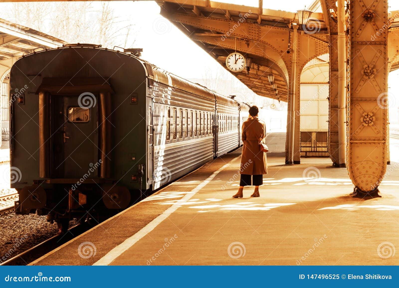 Une jeune femme se tient sur la plate-forme sous l horloge de station
