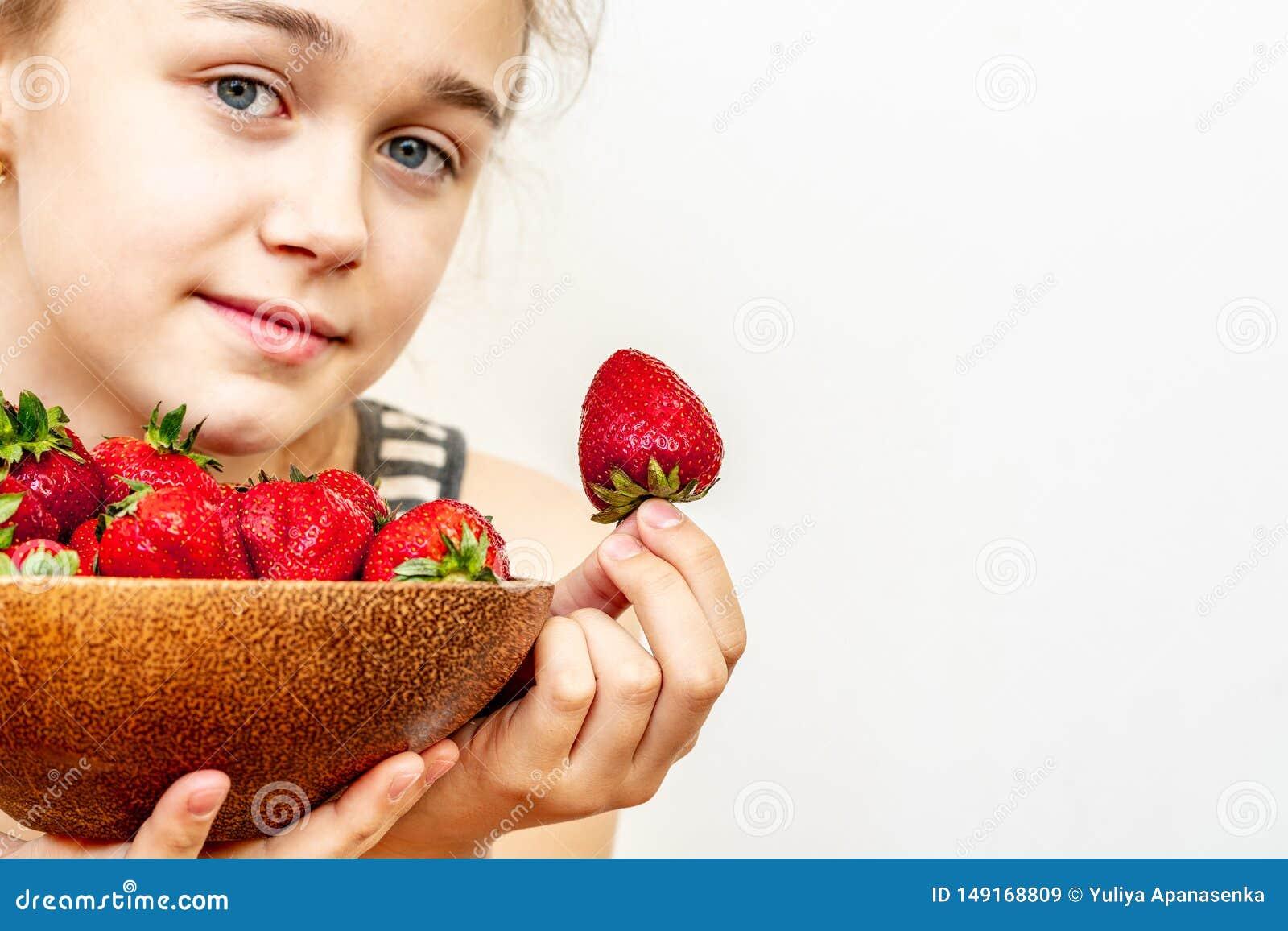 Une jeune femme tient un bol de fraises