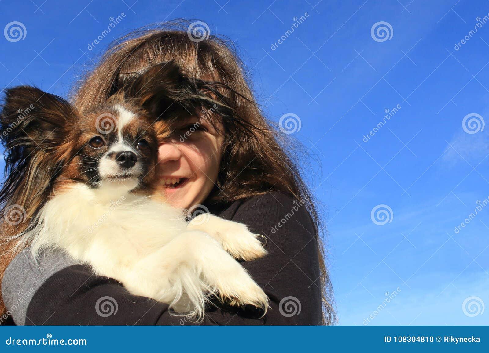 Une jeune fille avec de longs cheveux bruns tient un petit chien velu