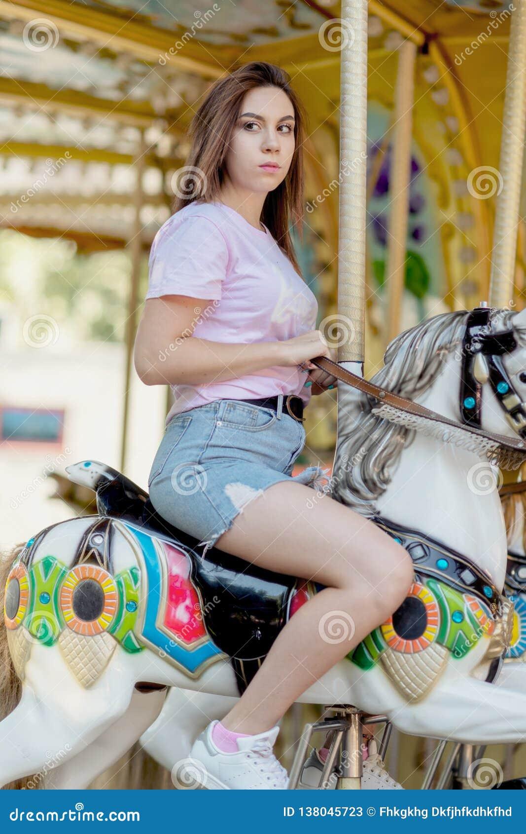 Une jeune fille avec des verres montant sur des chevaux d un carrousel