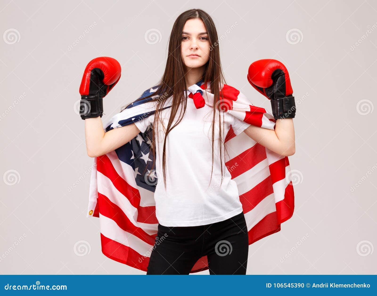 Une jeune fille, couverte de drapeau américain et habillée dans des gants de boxe