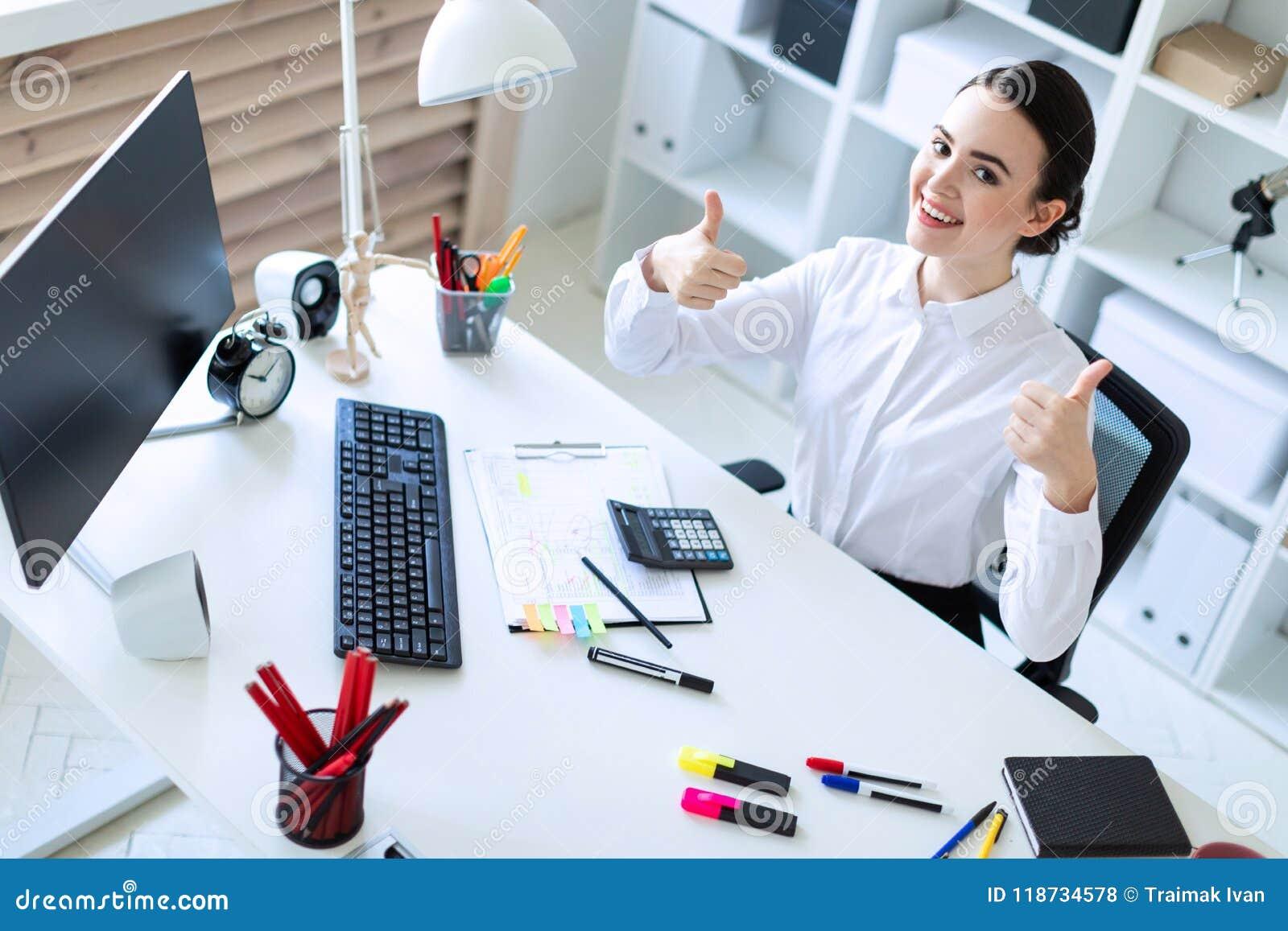 Une jeune fille dans le bureau s assied à une table travaille à
