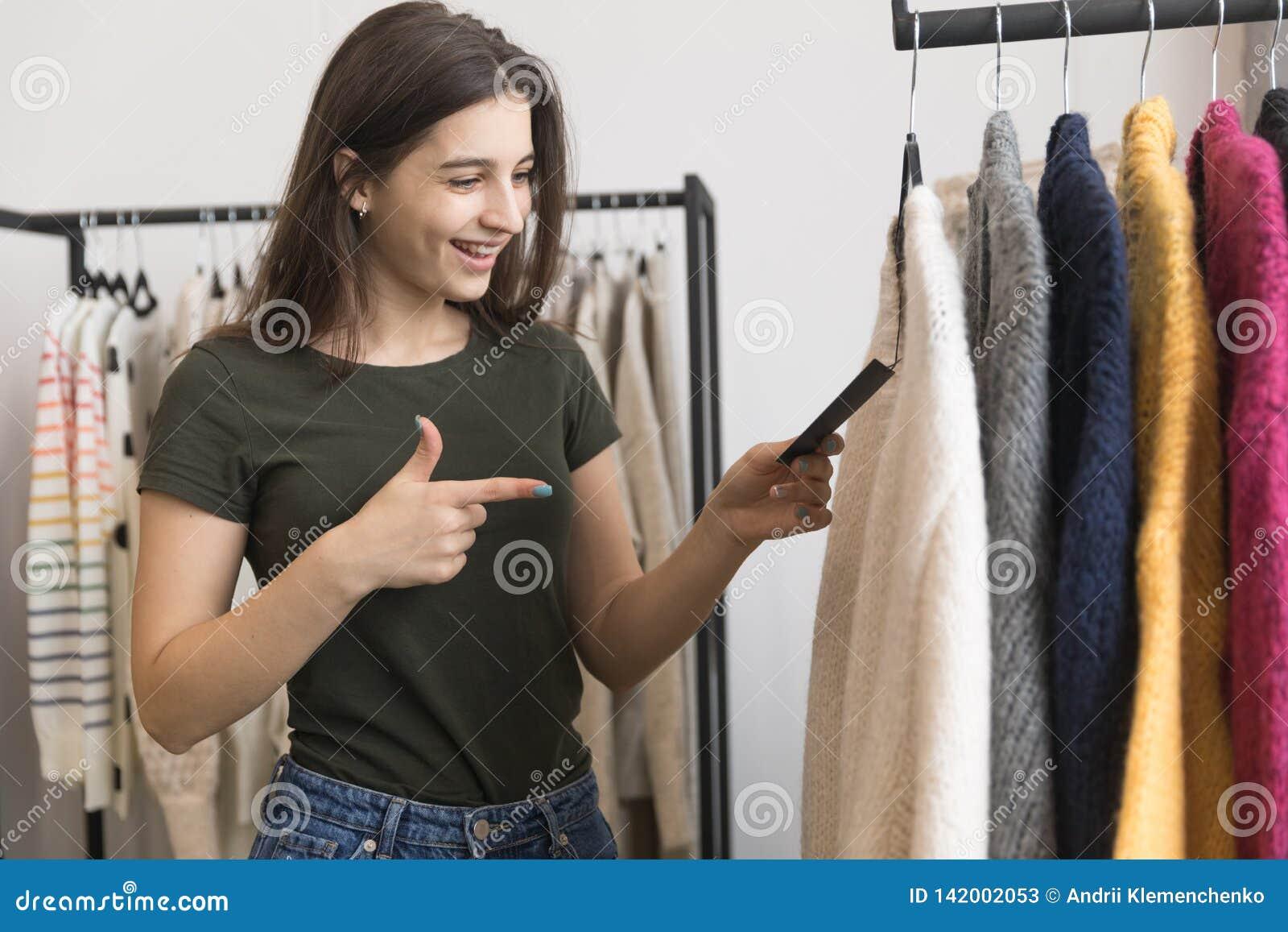 Une jeune fille dans un magasin d habillement, choisit un chandail
