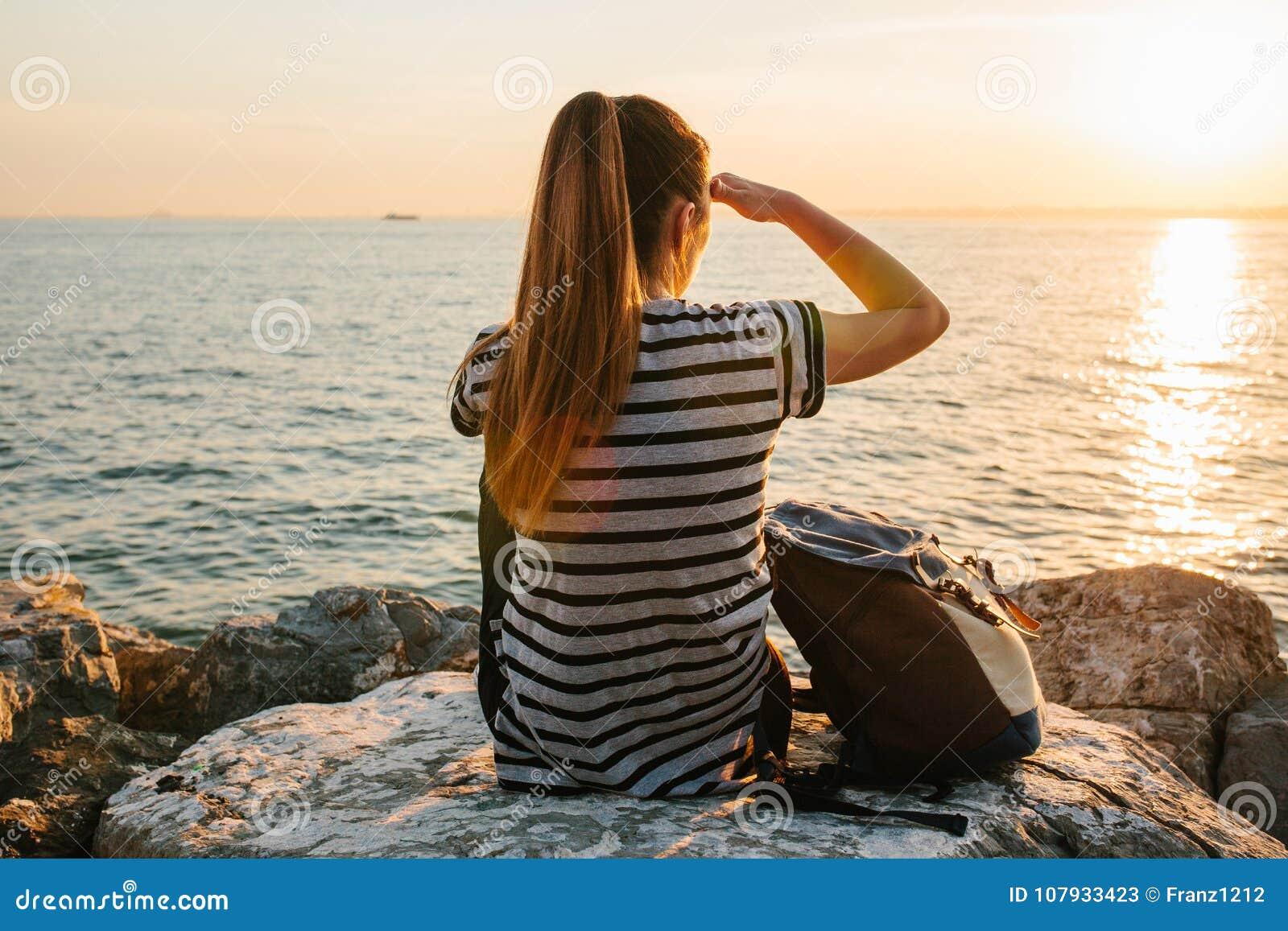 une jeune fille de touristes avec un sac dos s 39 assied sur les roches c t de la mer au. Black Bedroom Furniture Sets. Home Design Ideas