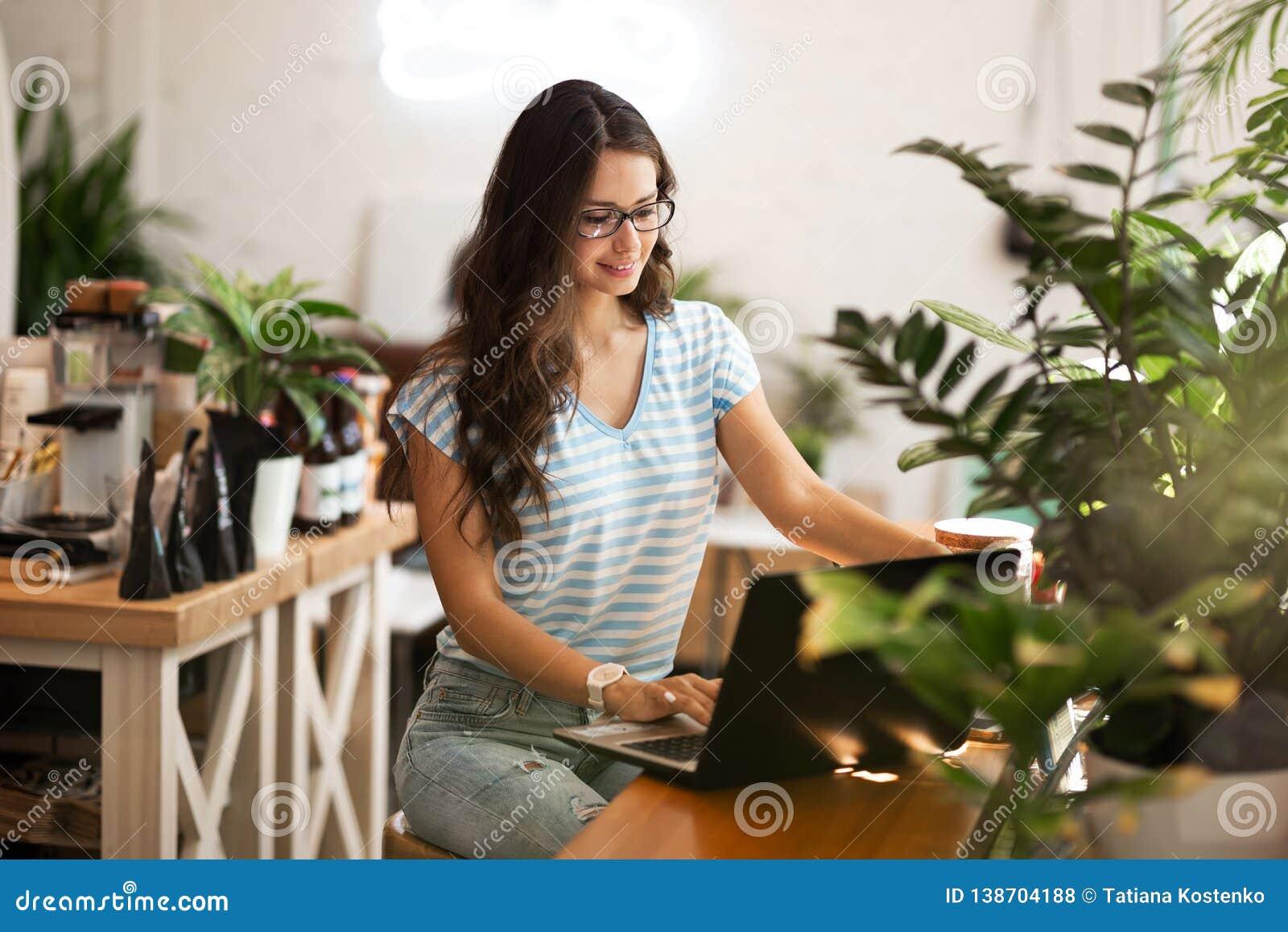 Une jeune fille mince avec les cheveux foncés et les verres, style occasionnel de port, s assied à la table et tient une tasse de
