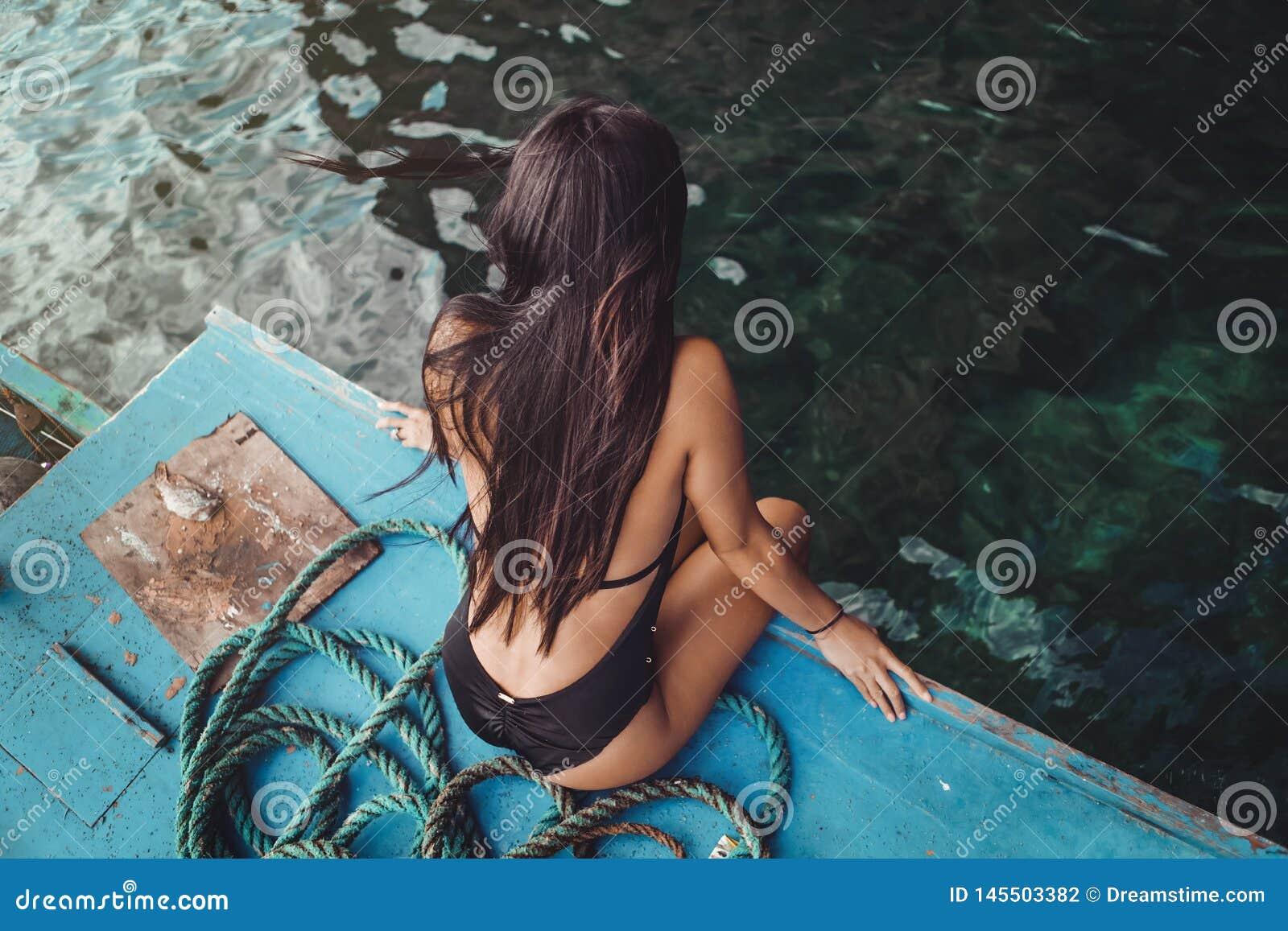 Une jeune fille philippine sexy s asseyant sur un bateau de p?che avec son maillot de bain noir appr?ciant la brise d oc?an aux P