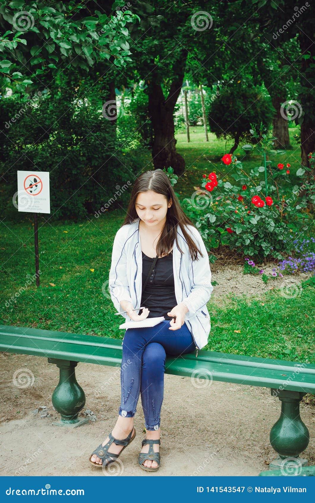 Une jeune fille s assied sur un banc dans le jardin et dessine