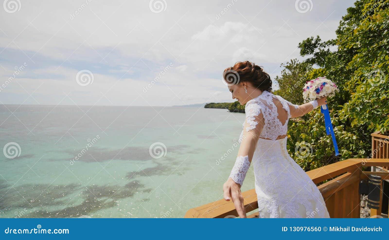 Une jeune mariée éblouissante apprécie le bonheur de la taille du balcon donnant sur l océan et les récifs Vol de l amour exotiqu