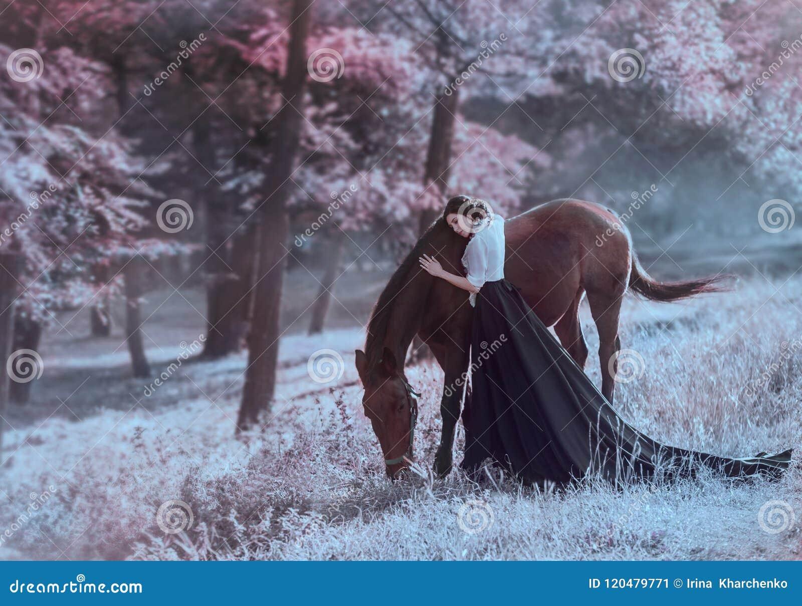 Une jeune princesse dans une robe de vintage avec un long train, avec la tendresse et amour, étreint son cheval La fille de brune