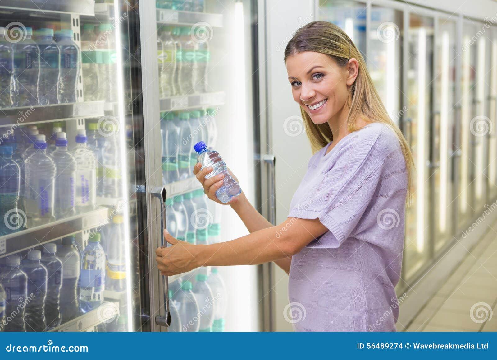 Une jolie eau de achat de sourire de femme blonde
