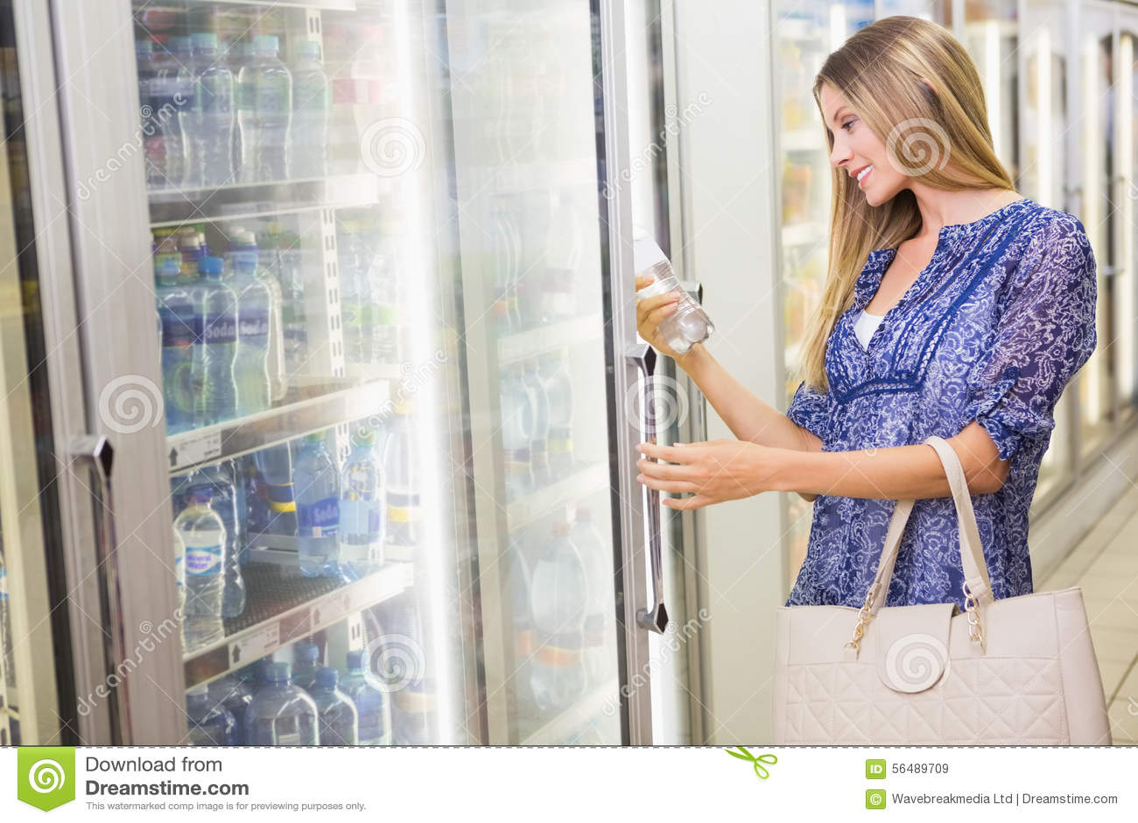 Une jolie femme blonde de sourire achetant les produits congelés