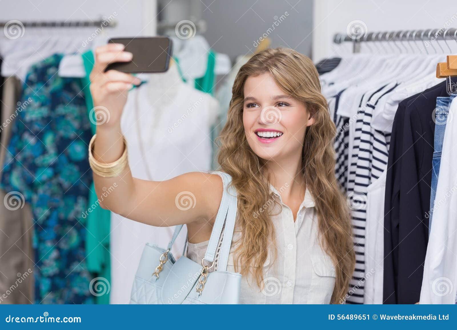 Une jolie femme blonde de sourire prenant des selfies