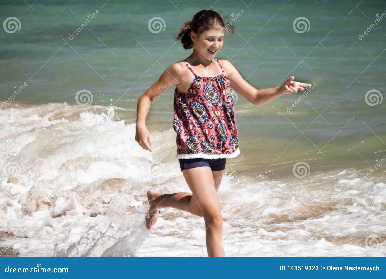 Une jolie fille courant dans les vagues sur la plage, brouillée, concept d été