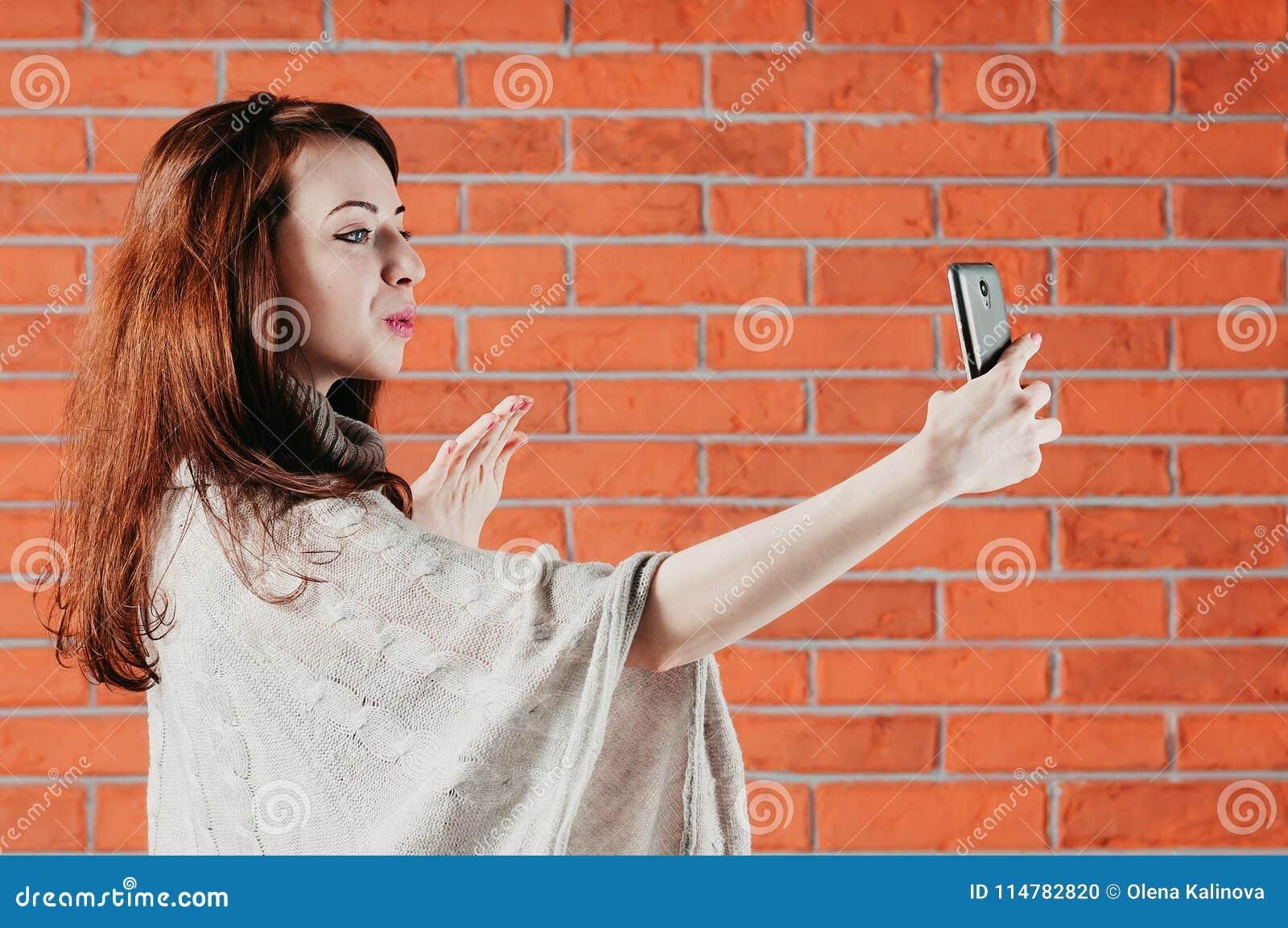 Une jolie fille fait le selfie avec le smartphone, envoyant le baiser d air