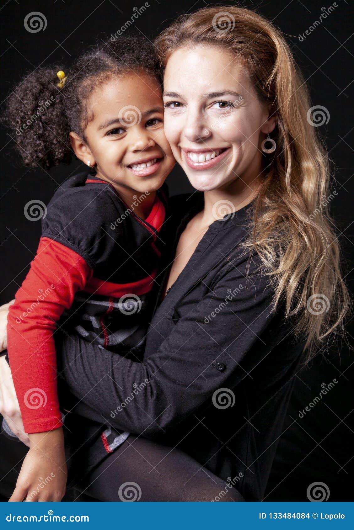 Une mère de famille avec l enfant de fille posant sur un studio noir de fond